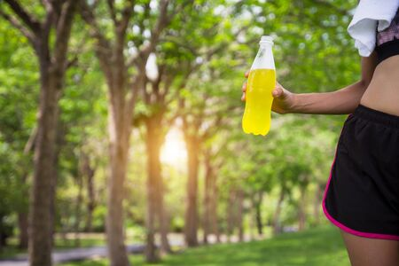 Female runner standing in park outdoors holding mineral water bottle, close up. Fitness athlete woman taking a break drinking water after running workout exercising.