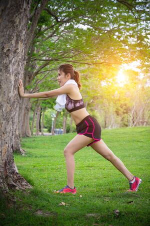 Athlete woman stratching before jogging outdoor, sporty girl exercises at sunny morning in park, healthy lifestyle concept.Female athlete taking break after running training or Runner Warming Up Before Running.