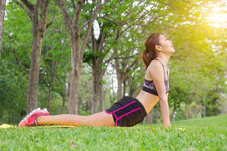 Young Asian woman pose practicing yoga in beautiful nature. Meditation in morning sunny day in green park. Sport ghalth care lifestyle concept.