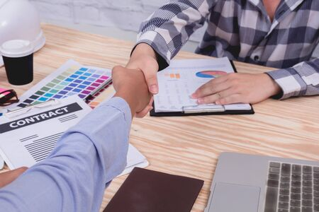 Business partner sitting shaking hands each other, finishing up meeting. Businessman holding hands to cooperation after signing deal contract agreement at office working. successful deal concept.