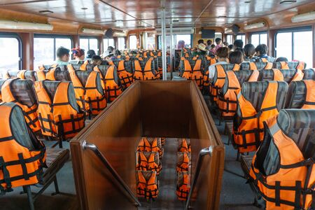 Life jacket orange color hanging on row on boat trip to island. Life jackets, safety equipment prevent drowning. life security tool in water.