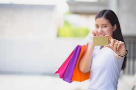 Young asian woman holding credit card and shopping bag in background with copy space. Woman showing credit card shopping lifestyle concept.