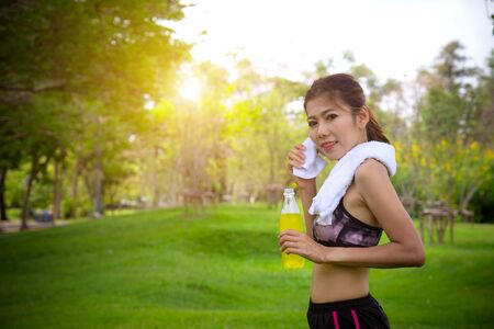 Female runner standing in park outdoors holding mineral water bottle. Fitness athlete woman taking a break drinking water after running workout exercising.