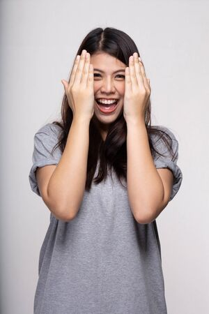 Happy Asian girl excited. Young woman smiling very happy surprised holding head open mouth showing face being amazed on grey background. cheerful smile female model having fun joyful.