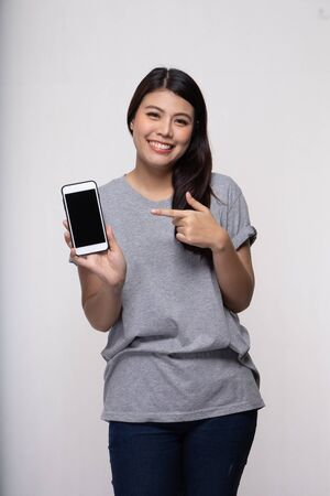 happy woman holding smartphone pointing finger on blank screen over white background.