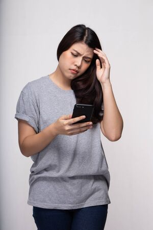 Young stressed woman using mobile phone text sms.  Asian girl holding cellphone typing text message with serious face. Technology people concept.