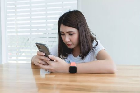 Young woman typing text message on smart phone in cafe. Asian girl wearing smart watch hand holding cellphone reading incoming sms message notification connected free wifi in coffee shop table.