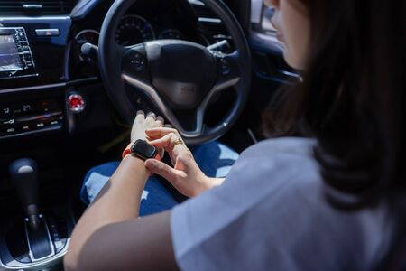 Young woman sitting in car setting smart watch touching button and touchscreen using mobile phone application. Female driver looking at smart watch black screen. Technology gadget people concept.