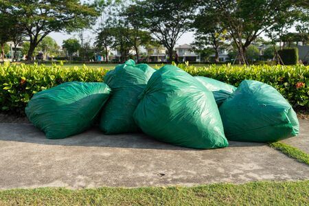 Garbage pile green plastic bags and trash waste pollution. Stack of junk black plastic bags packaging container for recycle. Green plastic bin garbage bags in dump land on floor. Rubbish background concept.