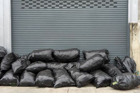 Garbage pile black plastic bags and trash waste pollution. Stack of junk black plastic bags packaging container for recycle. Black plastic bin garbage bags in dump land on floor. Rubbish background concept.