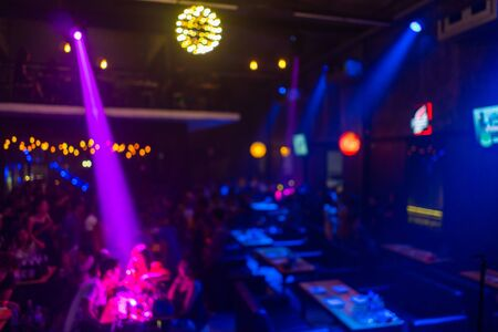 Blurry People hang out in night club.Friends enjoying party. Happy young people having fun at nightclub.