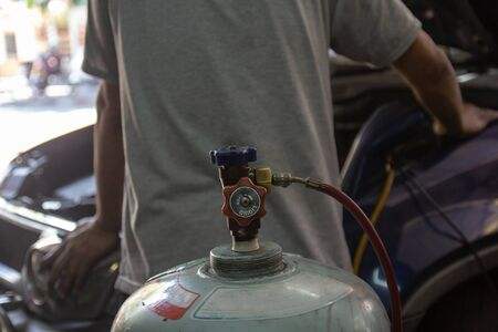 Close up Tank valve of freon bottle with Auto mechanic worker with tools for refuel fixing evaporator coil air condition in car garage in background. Maintenance service, checking and repair vehicle engine system.