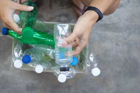 Hand  holding clear and green recyclable plastic bottle putting in paper garbage bin for recycling.waste management and plastic reuse toenvironmental protection world concept.