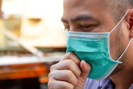 Asian man wearing protective face masks coughing. Sick man with flu wearing mask and blowing nose, epidemic flu concept.