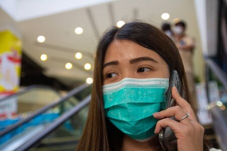 Asian woman wearing protective face masks against air pollution (PM2.5), prevent Coronavirus and talking on phone in public mall.