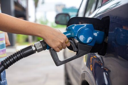 Blue car at gas station filled with fuel. Closeup woman hand pumping gasoline fuel in car at gas station.