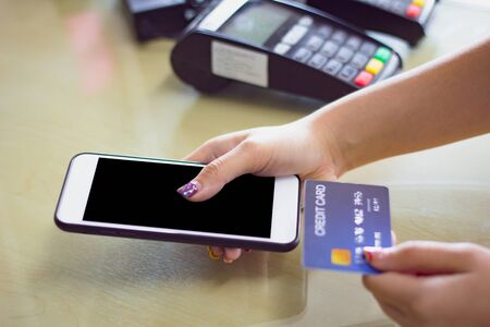 Woman hand holding smart mobile phone using credit card for mobile banking or paying online shopping.Female customer hands holding card and pay on credit card reader machine at shop counter.Credit card payment, buy and sell products & service concept.