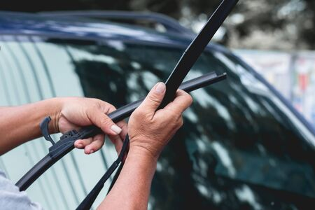 Mechanic replace windshield wipers on car. Replacing wiper blades