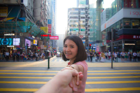 HONG KONG - Sepember 30, 2018: iSquare Shopping Mall in Tsim Sha Tsui, Hong Kong, China.People at cross road iSquare shopping centre, Kowloon downtown city. Young joyful Asian woman turn back holding and pull man hand lookingat camera with happy smile f