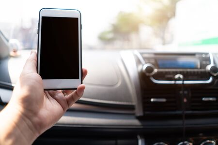 Hand holding mobile phone in car. man sitting in car holding phone. People using smart phone using map gps navigation,transportation and vehicle concept. 版權商用圖片