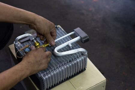 Car air conditioner evaporator coil close up.? Auto mechanic worker fixing air condition in car garage.Maintenanceservice, Repair checking vehicle engine tools car air conditioner system.