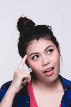 Young woman thinking, using finger pointing on head over white background.