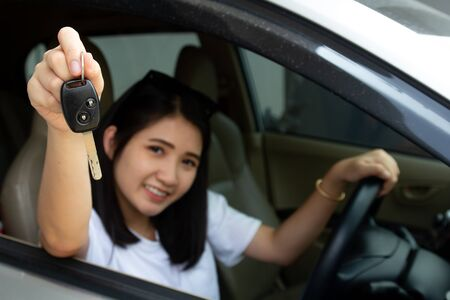 Asian car driver woman smiling showing new car key.Happy young girl owner taking car key from dealer in auto showroom. Auto business, sale or rent car and people success driver license concept. Stok Fotoğraf