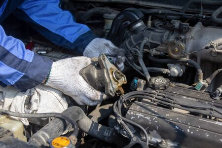 Check engine ignition system and change ignition coil. Car care service.Replacing ignition coil and spark plugs.Car mechanic fixing ignition coil on gasoline engine,  four-cylinder internal combustion engine. Stok Fotoğraf