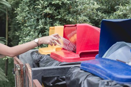 Woman drop plastic bottle into recycle bin.Waste separation trash for different kind of garbage before drop to bin to save the world, environment care.Pollution recycling management concept. Stok Fotoğraf