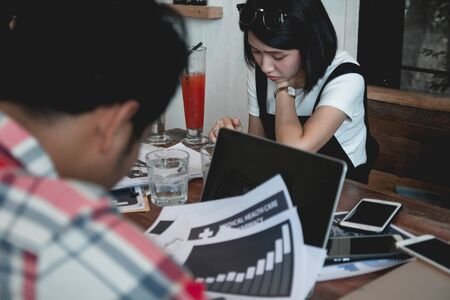 Stressed young woman in casual dress working on table at office with colleague.