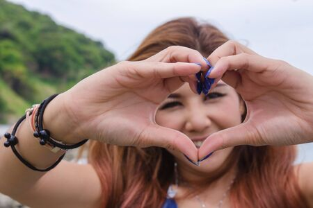 Happiness woman showing hands heart shape love sign. Happy smiling woman shows gesture heart with fingers. Young asian girl making heart symbol with hands looking at camera.