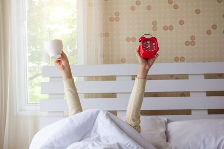Woman arm hands holding coffee cup and blue alarm clock in on bed in bed room. Young girl with two hands holding blue clock and cup, drinking coffee after awaking. wake up with fun in morning concept. Stock Photo