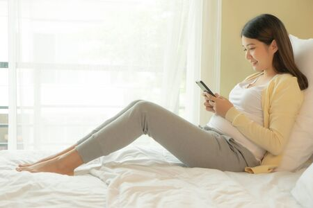 Young Asian pregnant woman using mobile phone in bedroom.