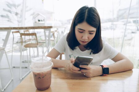 Young Asian woman using smartphone with smart watch on hand in coffee shop.Japanese girl wearing smartwatch texting on mobile phone in  cafe, modern city technology lifestyle concept.