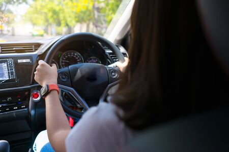 Female hands with smart watch on car steering wheel while driving on the road. People, driving, transport concept.