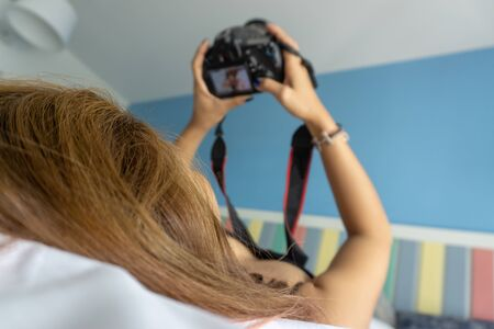 Young woman lying on bed holding dslr camera looking photos in camera in bedroom. blured, soft focus.