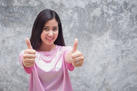 Young happy woman showing thumb up finger positively. Focus on face.Asian girl giving thumbs up hand on gray background.Female making thumb up sign and smiling cheerfully feeling good, support and respect gesture. Stok Fotoğraf