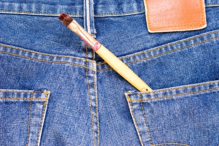 Art brush in a back pocket of a pair of blue jeans