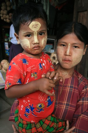 burmese mother carries son on her arm on May 25, 2007. in Yangon, Myanmar