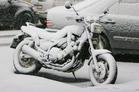 motorcycle wheel: Motorcycle covered with snow at outdoor parking