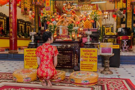 malaysia culture: beautiful woman in red chinese suit make merit pay respect to buddha in joss house public