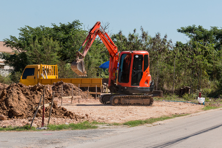 mini backhoe dig the ground hole for build new house Stock fotó