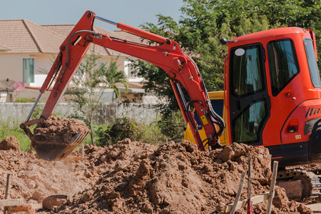 mini backhoe dig the ground hole for build new house Imagens