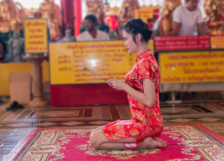 beautiful woman in red chinese suit make merit pay respect to buddha Stock Photo