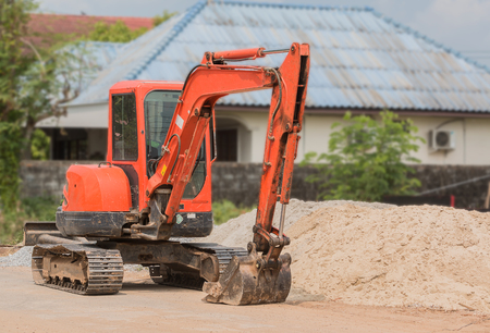 mini backhoe dig the ground hold and operate for build and construction Stock Photo