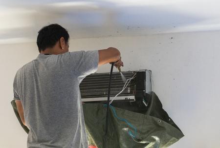 Le réparateur fait pour l'entretien de l'air conditionné dans la maison et pulvérise de l'eau, souffle pour nettoyer le filtre, est destiné aux soins de santé