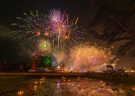 Firework in Loykratong and candle festival at Sukhothai province, Thailand, old buddha and pagoda is front background