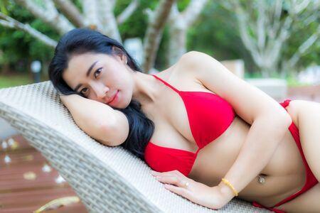 A beautiful woman long dark hairs in red bikini near the pool /and red bikini fashion in summer season