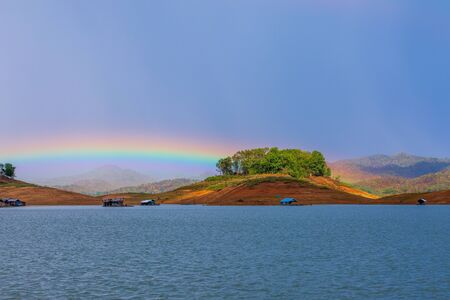 The beautiful rainbow show on rainy stop over the mountains and raft in lake 版權商用圖片