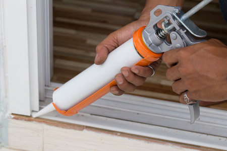 Side view of craftsman using glue with silicone gun